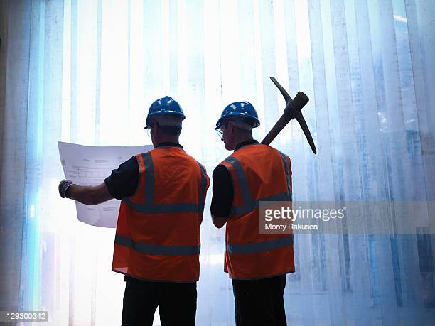 Silhouette of workers holding plans and a pickaxe