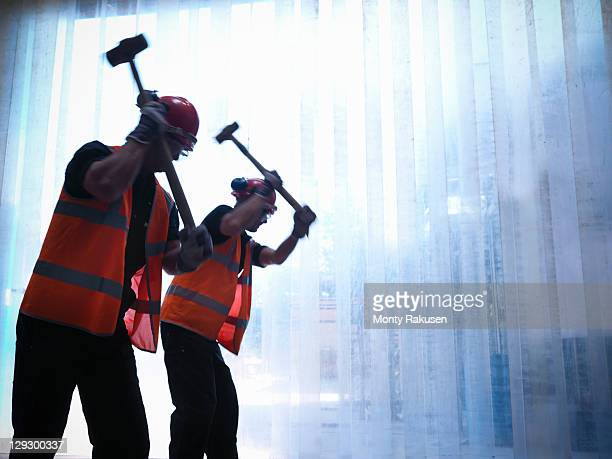 Silhouette of workers swinging hammers