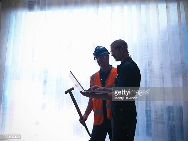 Silhouette of workers with laptop and spade