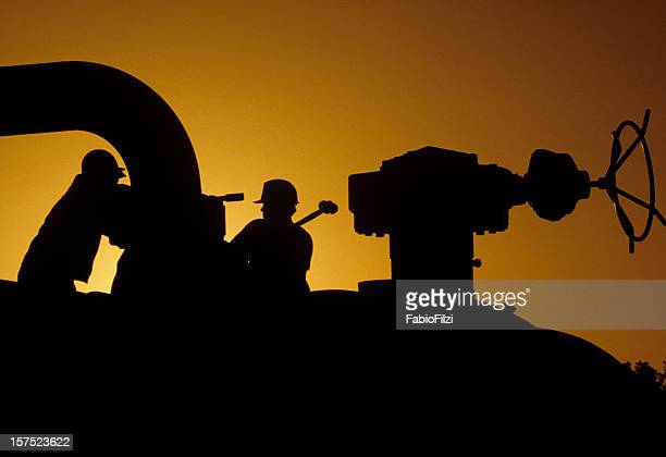 Silhouette of workers working on site at sunset