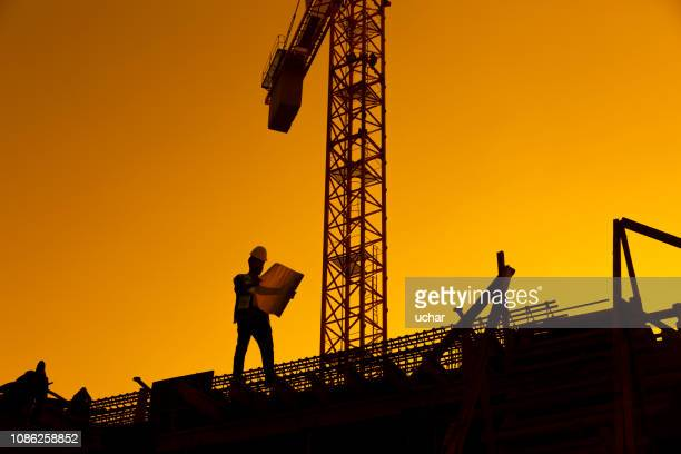 silhouette of working man standing with his planning paper - civil engineering stock pictures, royalty-free photos & images
