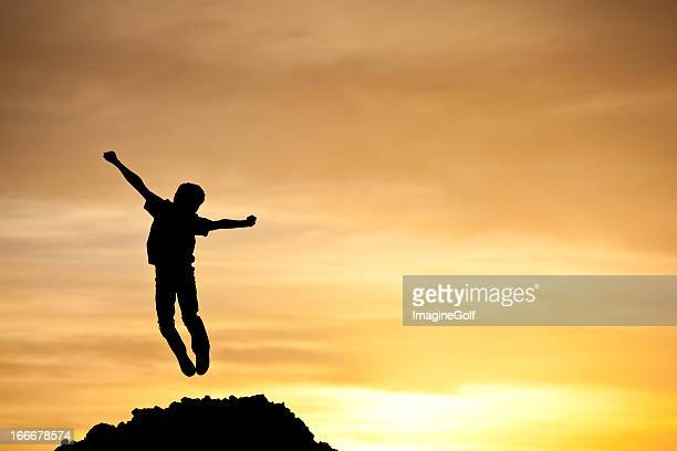 Silhouette of Young Boy Jumping for Joy