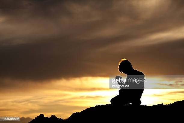 silhouette of young caucasian boy praying - god stock pictures, royalty-free photos & images