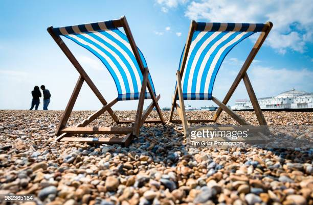 silhouette of young couple and two empty deck chairs and the palace pier, brighton - coastline stock photos and pictures