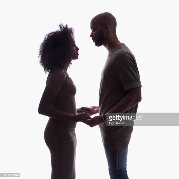silhouette of young couple in studio setting - black sexual stock photos and pictures