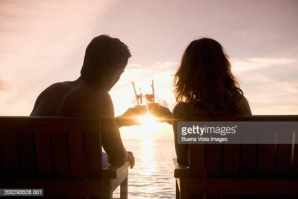 Silhouette of young couple sitting on chairs, toasting cocktails and looking out to sea at sunset, rear view
