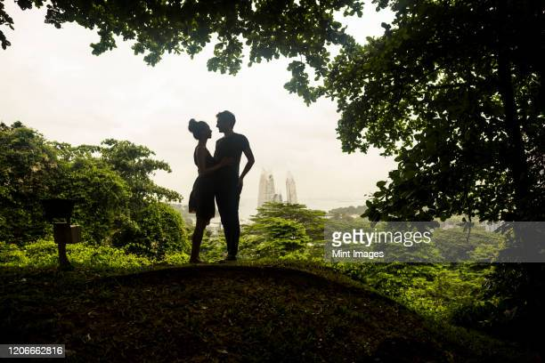 silhouette of young couple standing underneath trees in a forest, skyscrapers in the distance. - 愛 ストックフォトと画像