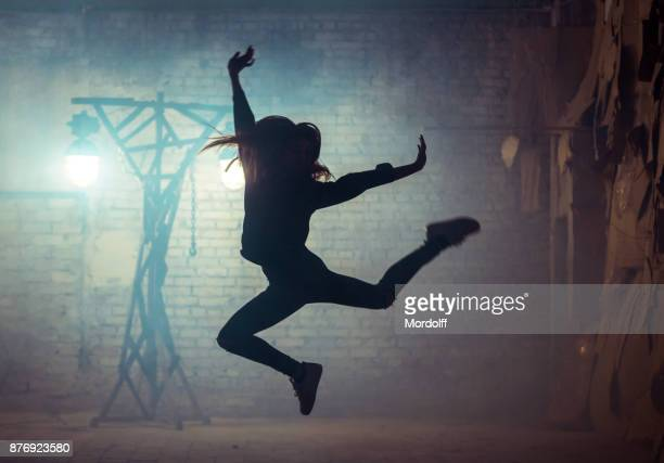silhouette of young female street dancer - dancing stock pictures, royalty-free photos & images