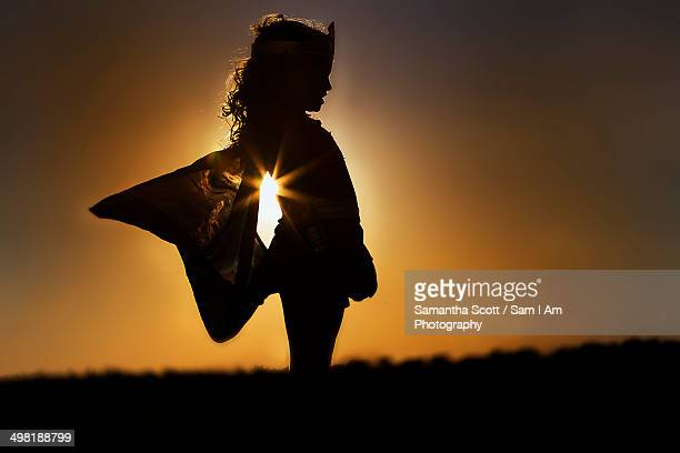 Silhouette of young girl in winged fairy costume at sunset