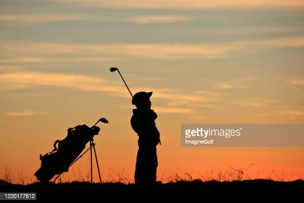 silhouette of young junior golfer making a swing - junior level stock pictures, royalty-free photos & images