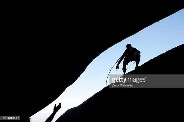 Silhouette of young male climbers reaching out for each other on rock