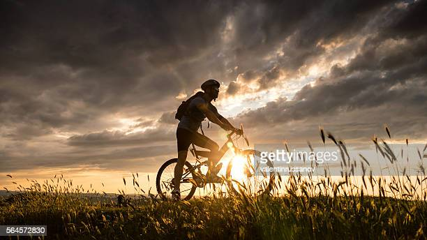 Silhouette of young man cycling on top of the hill