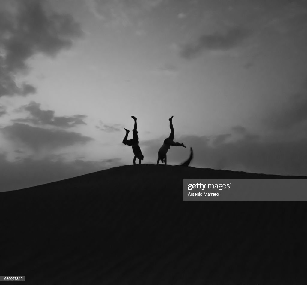 Silhouette Of Young Man Jumping in a dune in Mahmid Morocco : Stock Photo
