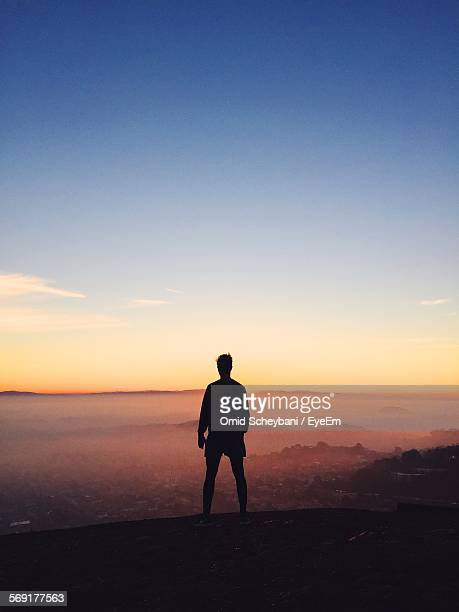 Silhouette of young man looking at cityscape at dusk