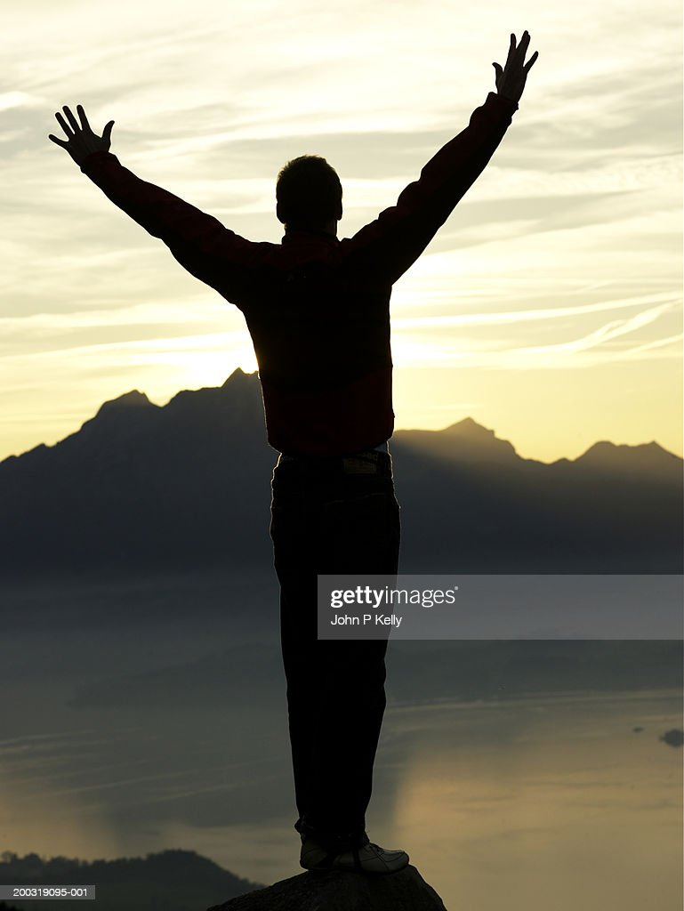 silhouette of young man on rock facing mountain sunset rear view