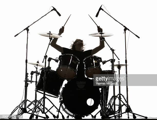 Silhouette of young man playing drums, arms raised, head back