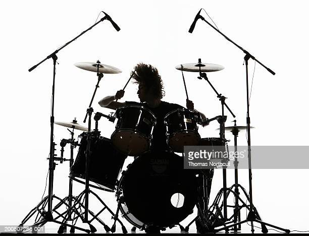 Silhouette of young man playing drums, tossing hair