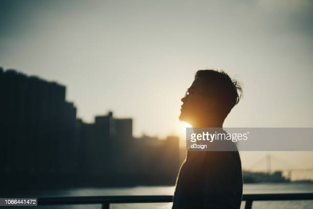 silhouette of young man standing against urban cityscape and harbour looking up to sky in deep thought at sunset - backlit stock photos and pictures