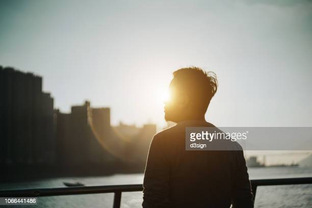 silhouette of young man standing against urban cityscape and harbour looking up to sky in deep thought - gegenlicht stock-fotos und bilder