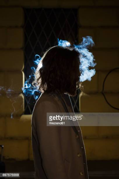 Silhouette of young man surrounded by a cloud of smoke outdoors at night