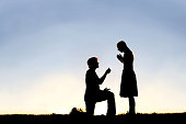 Silhouette of Young Man with Engagement Ring Proposing to Woman