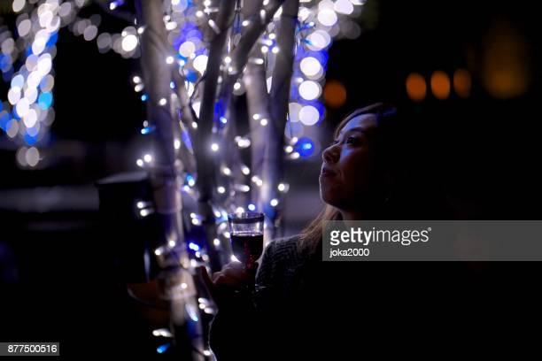 クリスマスの照明を通り decolatd で若い女性のシルエット