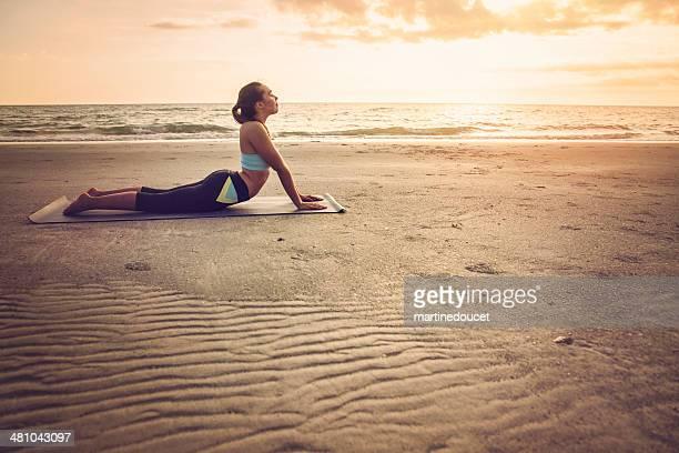 Silhouette de jeune femme faisant yoga sur la plage au coucher du soleil.