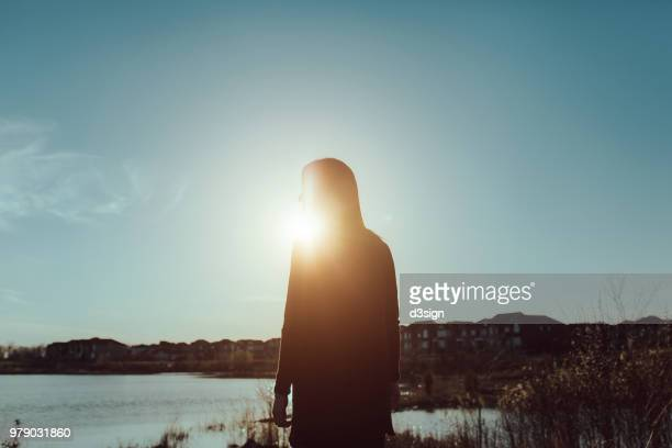 silhouette of young woman enjoying the freshness of air and warmth of sun by the sea at sunrise - 雰囲気 ストックフォトと画像