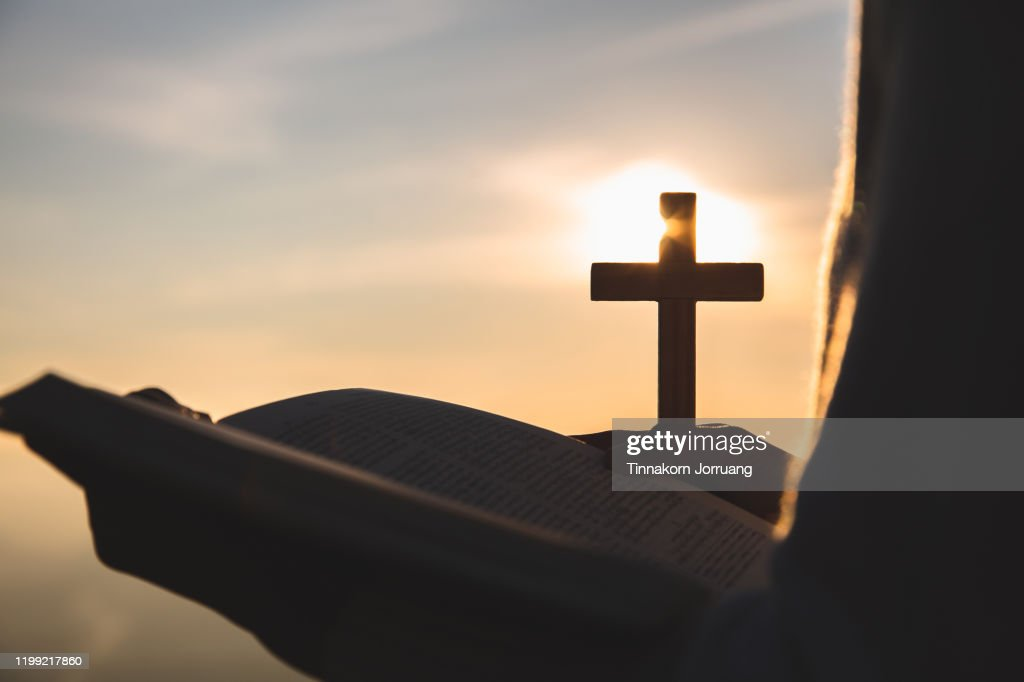 Silhouette of young woman hands holding holy Bible and lift of christian cross with light sunset background. christian concept : Stock Photo