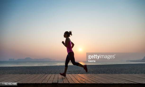 silhouette of young woman jogging on shore at sunrise - pink shoe stock pictures, royalty-free photos & images