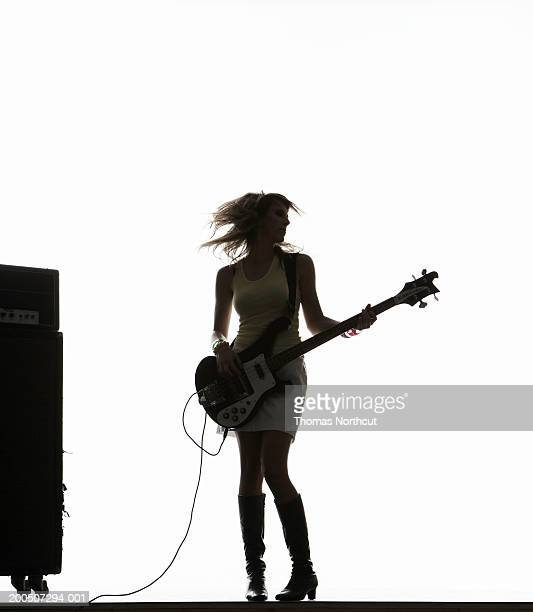 Silhouette of young woman playing bass guitar and tossing hair