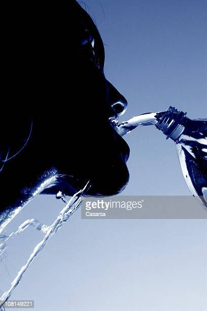 SIlhouette of Young Woman Pouring Water Into Mouth, Toned