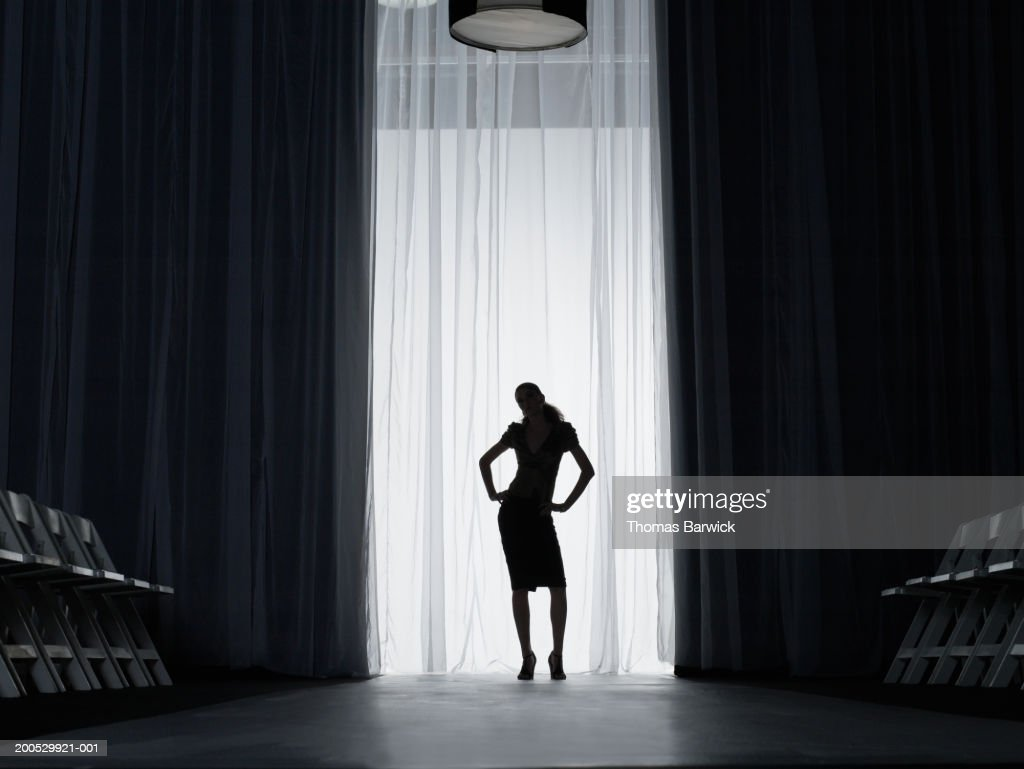 Silhouette of young woman standing on catwalk, hands on hips : Stock Photo