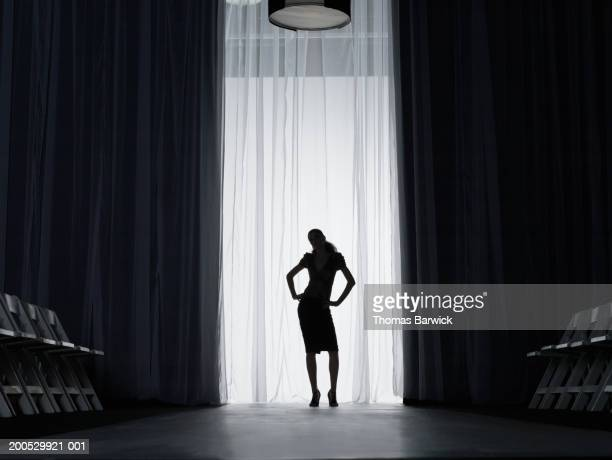 silhouette of young woman standing on catwalk, hands on hips - sfilata di moda foto e immagini stock