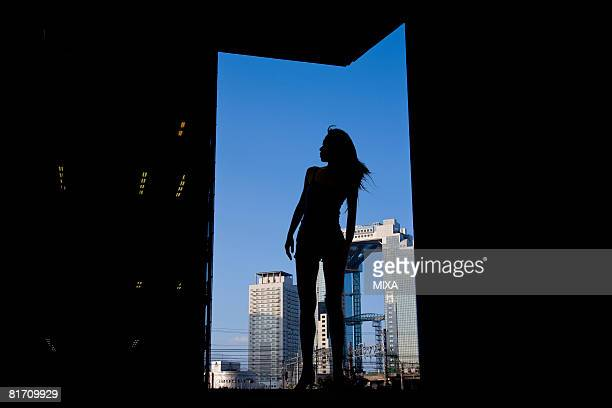 Silhouette of young woman standing