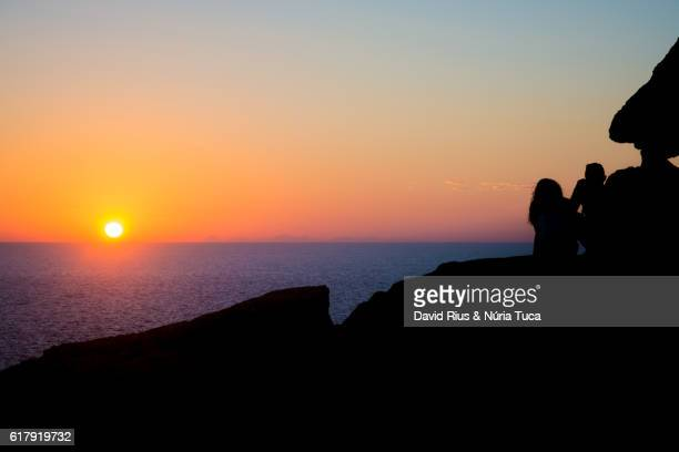 Silhouette of young woman taking a photo