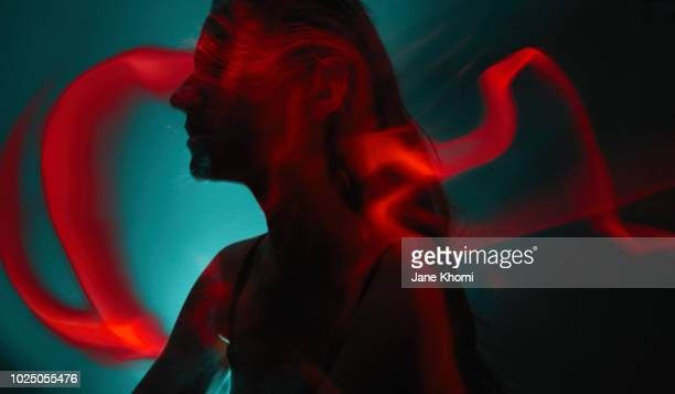 silhouette of young woman with light painting trails - fluorescent light stock pictures, royalty-free photos & images