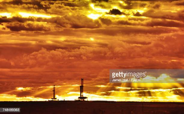 Silhouette Oil Pumps Against Cloudy Sky During Sunset