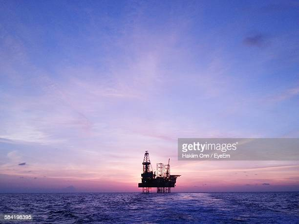 silhouette oil rig in sea against sky during sunset - oil rig stock pictures, royalty-free photos & images