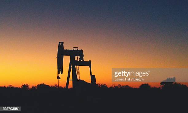 Silhouette Oil Well Pump In Field Against Sunset Sky