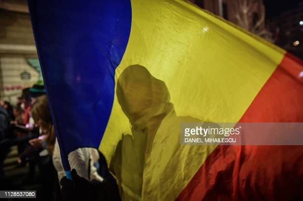 Silhouette on a Romanian flag is pictured as protesters march in downtown Bucharest demanding an independent justice system on March 3, 2019. -...