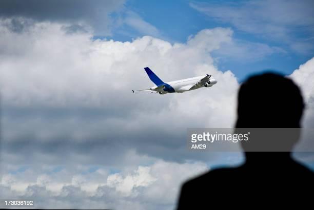 Silhouette on man watching plane take off
