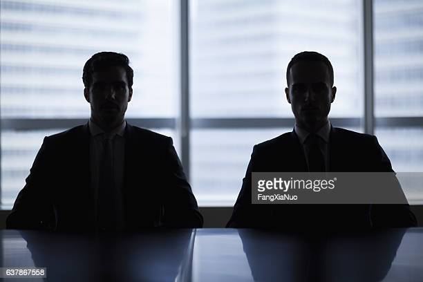 Silhouette pair of businessmen in meeting room