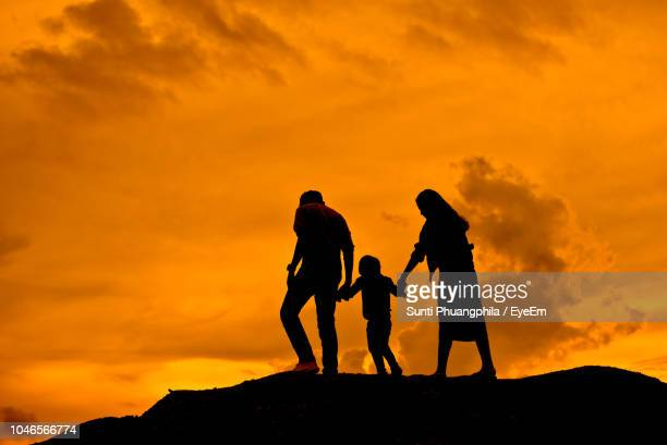 silhouette parents walking with son on mountain against orange cloudy sky during sunset - family with one child stock pictures, royalty-free photos & images