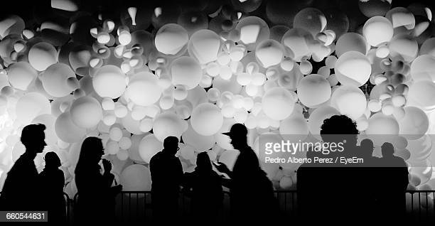 Silhouette People Against Balloons At Night