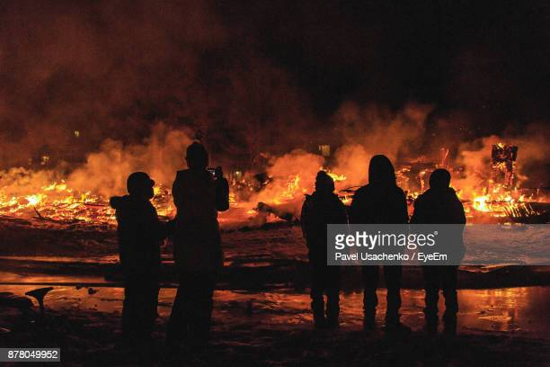 silhouette people against fire at night - burns night stock pictures, royalty-free photos & images