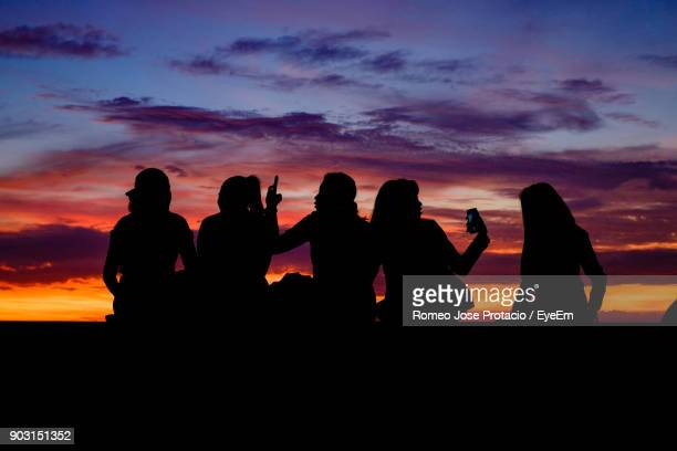 silhouette people against sky during sunset - manila bay stock photos and pictures