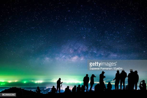 Silhouette People Against Star Field At Night
