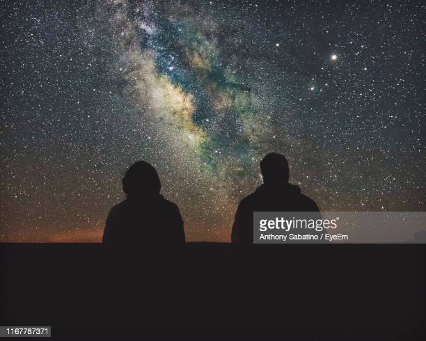 silhouette people against start field - astronomy stock pictures, royalty-free photos & images