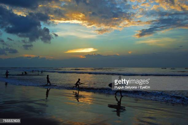 Silhouette People At Beach Against Cloudy Sky During Sunset